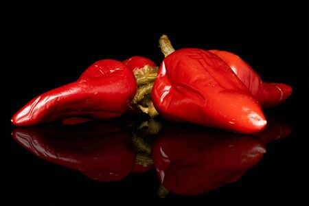 Group of four whole pickled red pepper isolated on black glass
