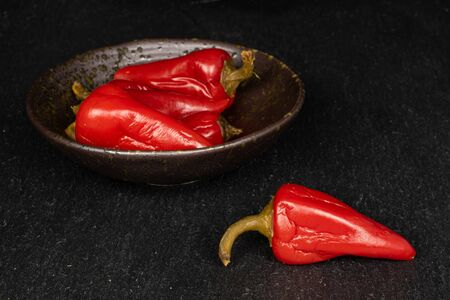 Group of four whole pickled red pepper in glazed bowl on grey stone