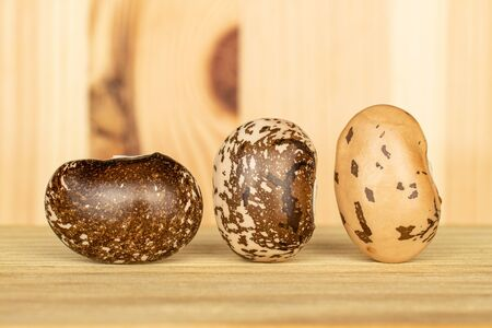Group of three whole speckled brown bean pinto on natural wood