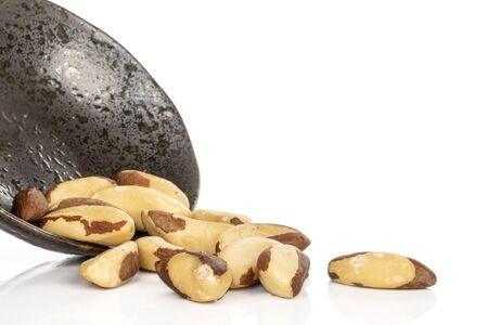 Lot of whole hulled brazil brown nut in glazed bowl isolated on white background Stock Photo