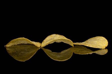 Group of three whole crisp potato chip isolated on black glass