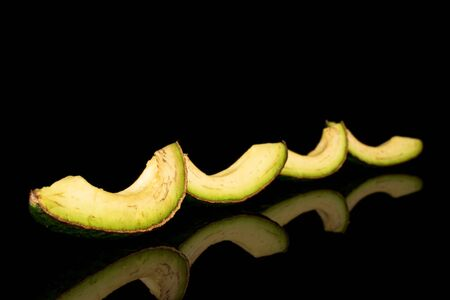 Group of four slices of fresh green avocado isolated on black glass