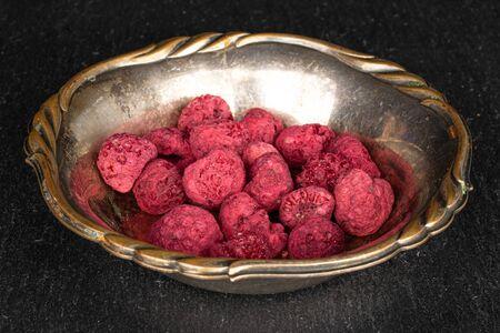 Lot of whole dried raspberry in copper bowl on grey stone Reklamní fotografie