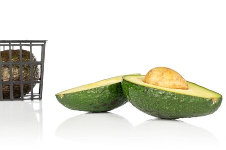 Group of one whole two halves of fresh green avocado in black plastic basket isolated on white background