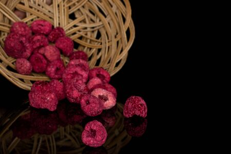 Lot of whole dried raspberry in round rattan bowl isolated on black glass