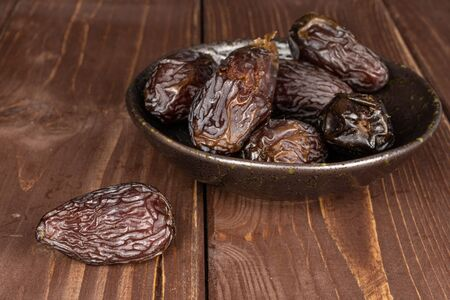Lot of whole dried brown date fruit in glazed bowl on brown wood