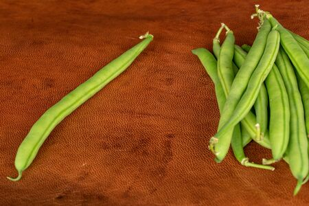 Lot of whole snap green bean on cognac leather Stock fotó