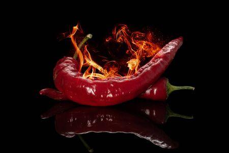 Dos pimientos rojos frescos ardientes aislados en vidrio negro