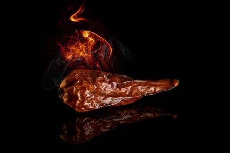 One burning dry hot pepper isolated on black glass