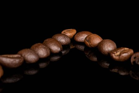 Lot of whole fresh coffee bean isolated on black glass