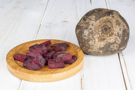 One whole lot of pieces of raw sweet beetroot on round bamboo coaster on white wood Standard-Bild