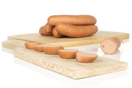 Group of four whole five slices one piece of pork frankfurt sausage on bamboo cutting board on wooden cutting board isolated on white background Imagens