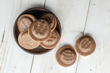 Group of seven whole chocolate biscuit with brown ceramic coaster flatlay on white wood