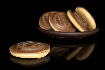 Group of five whole chocolate biscuit with brown ceramic coaster isolated on black glass