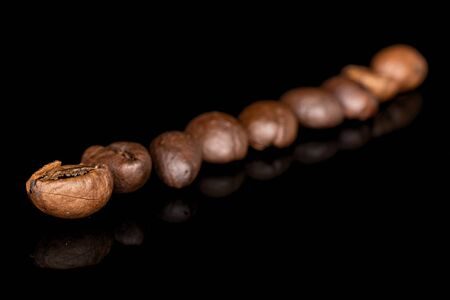 Group of nine whole fresh coffee bean isolated on black glass