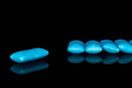 Group of five whole blue chewing gum isolated on black glass