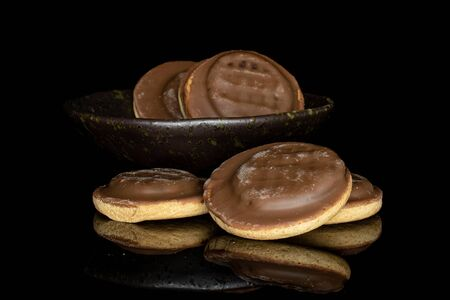 Lot of whole chocolate biscuit in glazed bowl isolated on black glass