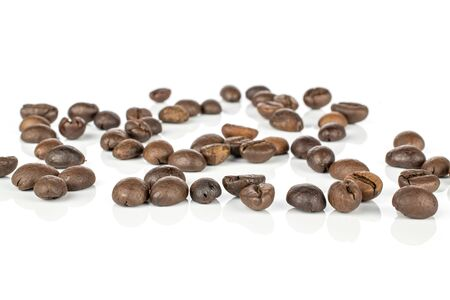 Lot of whole disordered fresh coffee bean isolated on white background Фото со стока