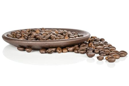 Lot of whole dark fresh coffee bean with brown ceramic coaster isolated on white background