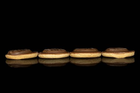 Group of four whole chocolate biscuit line isolated on black glass