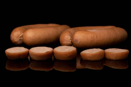 Group of four whole five slices of pork frankfurt sausage isolated on black glass Imagens