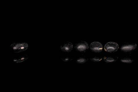 Groupe de six haricots noirs entiers isolés sur verre noir