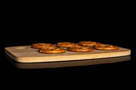 Group of six whole salty brown pretzel on bamboo cutting board isolated on black glass