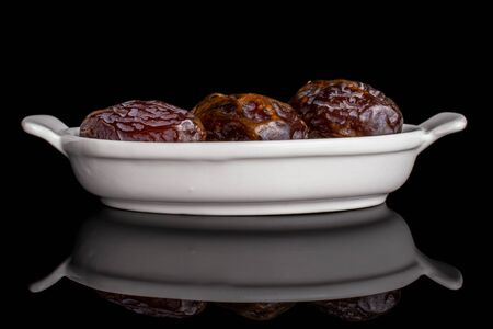 Group of three whole dry brown date fruit in white oval ceramic bowl isolated on black glass
