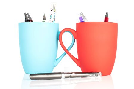 Lot of whole writing ballpoint pen with red ceramic cup and blue ceramic cup isolated on white background