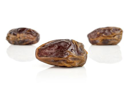 Group of three whole dry brown date fruit one is in the front isolated on white background