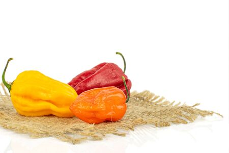 Group of three whole hot chili pepper on natural sackcloth isolated on white background Banco de Imagens