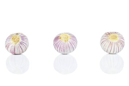 Group of three whole fresh purple single clove garlic in line isolated on white background