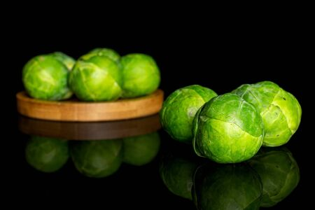 Group of eight whole fresh green brussels sprout on bamboo coaster isolated on black glass