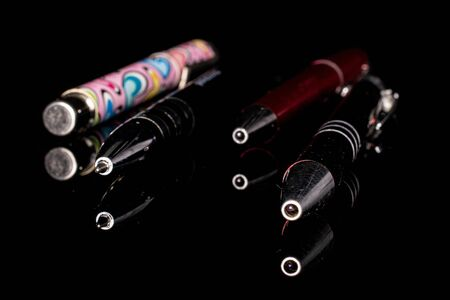 Group of four whole bright writing ballpoint pen isolated on black glass