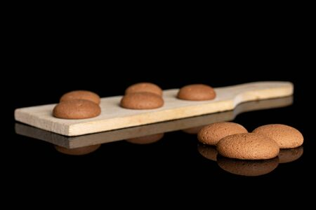 Group of eight whole sweet brown chocolate sponge biscuit on small wooden cutting board isolated on black glass Reklamní fotografie