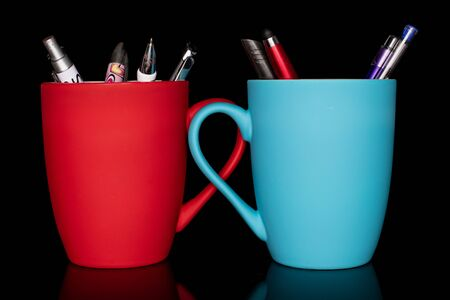 Lot of whole writing ballpoint pen with red ceramic cup and blue ceramic cup isolated on black glass