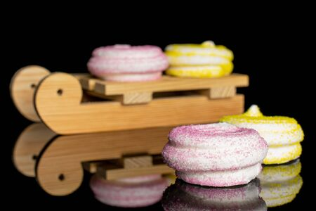 Group of four whole pink and yellow sweet meringue with wooden sledge isolated on black glass