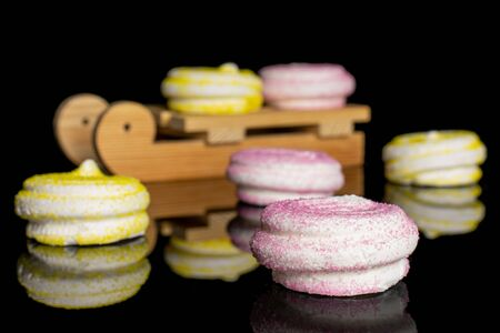 Group of six whole pink and yellow sweet meringue with wooden sledge isolated on black glass