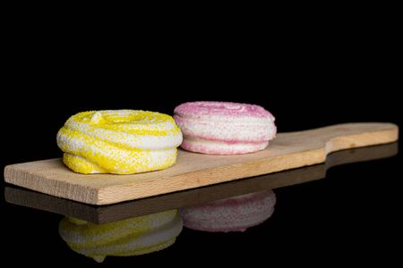 Group of two whole pink and yellow sweet meringue on small wooden cutting board isolated on black glass
