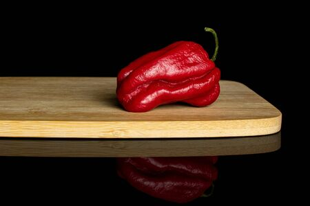 One whole hot chili pepper on bamboo cutting board isolated on black glass