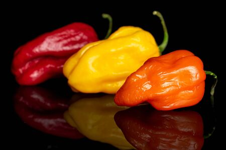 Group of three whole hot chili pepper placed diagonally isolated on black glass
