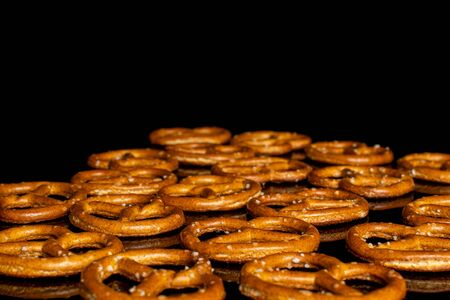 Lot of whole salty brown pretzel isolated on black glass