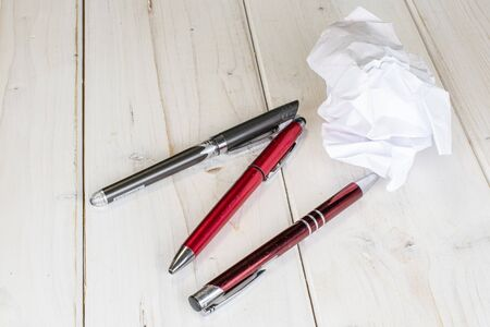 Group of three whole writing ballpoint pen with white paper on white wood