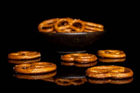 Lot of whole salty brown pretzel in dark ceramic bowl isolated on black glass Stock Photo