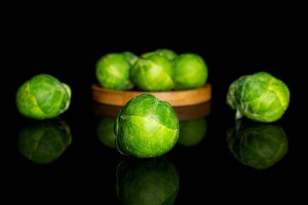 Group of eight whole fresh green brussels sprout on bamboo coaster isolated on black glass Reklamní fotografie - 140188208