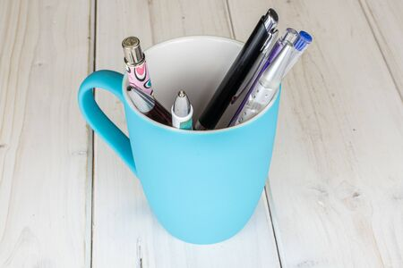 Group of seven whole writing ballpoint pen with blue ceramic cup on white wood Zdjęcie Seryjne