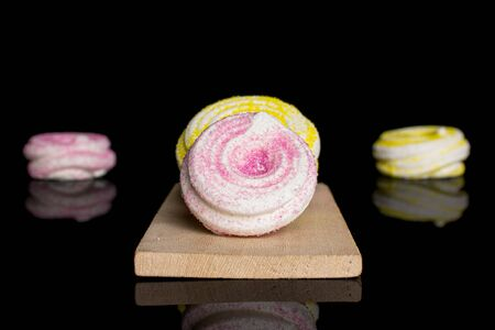 Group of four whole pink and yellow sweet meringue on small wooden cutting board isolated on black glass