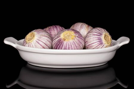Lot of whole fresh purple single clove garlic in white oval ceramic bowl isolated on black glass Reklamní fotografie