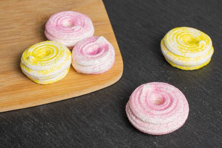 Group of five whole pink and yellow sweet meringue on bamboo cutting board on grey stone