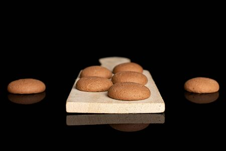 Group of seven whole sweet brown chocolate sponge biscuit on small wooden cutting board isolated on black glass